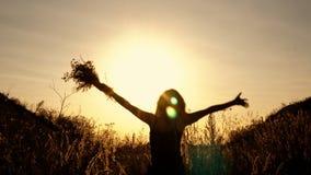 Svart kontur av en flicka på bakgrunden av en ljus solnedgång Hon hoppar och vinkar hennes händer bland blommorna i lager videofilmer