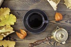 Svart kopp kaffe, hösteksidor, kruka för turkiskt kaffe på en träbakgrund cozy isolerad white för höst begrepp royaltyfri bild