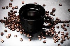 Svart kopp kaffe- och kaffefrö på kritiserabakgrunden Till Royaltyfri Bild