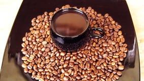 Svart kopp med varmt kaffe En kopp kaffe står på kaffebönorna i en svart platta stock video