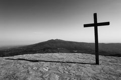 Svart kors med berg i bakgrund Arkivfoton