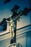 Svart kors med guld- jesus och kapellet som bakgrund Arkivbild