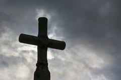 Svart kors mot mörk himmel Arkivfoton