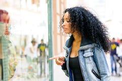 Svart kvinna afro frisyr som ser shoppafönstret Royaltyfri Fotografi