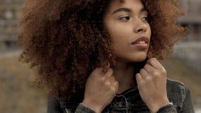 Svart kvinna för blandat lopp med stort afro lockigt hår i utomhus- stad stock video