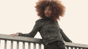 Svart kvinna för blandat lopp med stort afro lockigt hår i utomhus- stad arkivfilmer