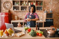 Svart kvinna i förkläde som lagar mat den sunda frukosten royaltyfri bild