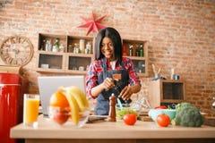 Svart kvinna i f?rkl?de som lagar mat den sunda frukosten royaltyfri foto