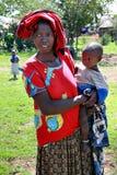 Svart kvinna i sjaskig kläder, håll ett barn Arkivfoto