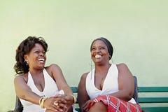 Svart kvinna med den vita klänningen som skrattar på bänk Royaltyfria Bilder