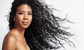 Svart kvinna med ett lockigt hår i luft royaltyfri fotografi