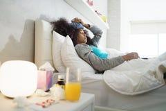 Svart kvinna med för influensa och den hållande ispåsen för förkylning Royaltyfria Foton