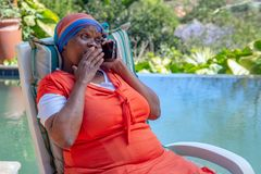 Svart kvinna med förvånat uttryck på hennes framsida och att rymma hennes hand till hennes mun, medan tala på en mobiltelefon royaltyfria bilder