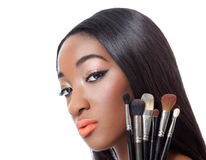 Svart kvinna med hållande makeupborstar för rakt hår Royaltyfri Foto