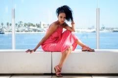 Svart kvinna med rosa färgklänningen och örhängen. Afro- frisyr Royaltyfria Bilder