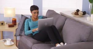 Svart kvinna som använder bärbara datorn på soffan royaltyfria foton