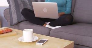 Svart kvinna som använder bärbara datorn på soffan royaltyfri bild