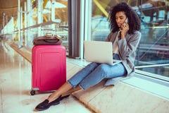 Svart kvinna som använder mobiltelefonen och bärbara datorn på flygplatssammanträdet royaltyfria foton