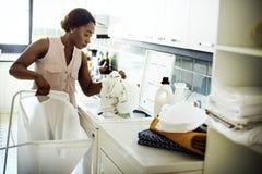 Svart kvinna som använder tvagningmaskinen som gör tvätterit Arkivfoton