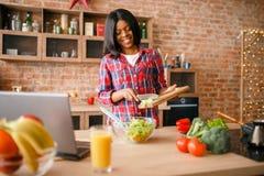 Svart kvinna som lagar mat sallad p? k?ket royaltyfri bild