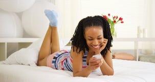Svart kvinna som ler och använder smartphonen på säng royaltyfri bild
