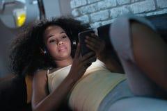 Svart kvinna som lyssnar till musik på telefonen på natten royaltyfria foton