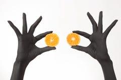 Svart kvinnas händer som rymmer orange halvor Svarta händer med den ljusa smakliga mandarinen royaltyfri foto