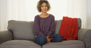 Svart kvinnasammanträde på soffan som ser kameran Fotografering för Bildbyråer