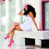 Svart kvinnawihklänning och sunhatt, afro frisyr Arkivbilder