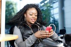 Svart kvinnlig lyssnande musik från telefonleklista Arkivfoto