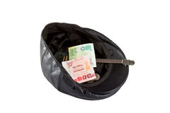 Svart läderhatt med donerade pengar som isoleras på vit Fotografering för Bildbyråer