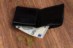 Svart läderplånbok med fem euro och eurocent Begrepp: pov Arkivbild
