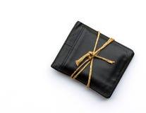Svart läderplånbok med rep på vit bakgrund mot som kroken för hang för dollar för bakgrundsbetebegrepp den gråa Royaltyfria Bilder