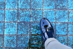 Svart lädersko för man med den bruna pedalen för höger fot för jeans ner mig Fotografering för Bildbyråer