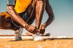 Svart löpareband hans skor på stranden royaltyfri foto