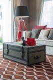 Svart lampa och soffa med casketen som tabellen på brun matta royaltyfri fotografi