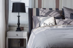 Svart lampa på grå färgtabellen i sovrum arkivfoto