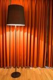 Svart lampa på ställning och den röda gardinen Arkivbild