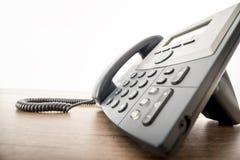 Svart landlinetelefoninstrument med ett nummerblock på en rusti Royaltyfria Bilder