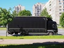 Svart lastbil på stadsgatan royaltyfri foto