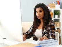 Svart le kvinna som sitter p? arbetsplatsen som arbetar med skrivbords- PC arkivbild
