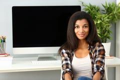 Svart le kvinna som sitter p? arbetsplatsen som ser kameran royaltyfria foton