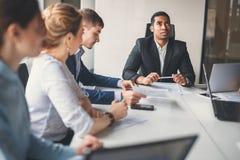 Svart ledare av affärsfolket som ger ett anförande i ett konferensrum Arkivfoton
