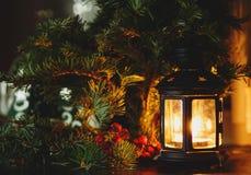 Svart lykta med stearinljusställningar bredvid granträd Vinterferier, nytt år och julberöm royaltyfria bilder