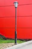 Svart lyktstolpe mot den röda väggen arkivbild