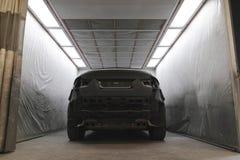 Svart lyxig bil för målningprocess Arkivbilder