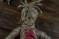 Svart magisk voodoodocka med röd hjärta Arkivbild