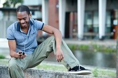 Svart Male lyssna till musik på Mp3 Arkivbild