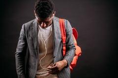 Svart man i lag och T-tröja som att bry sig rosa bagpack och väljer musik Arkivfoto