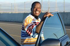 Svart man och hans bil Arkivbild